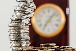 Pièces de monnaies et horloge illustrant un article sur l'Assurance-Vie